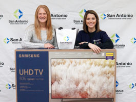 SACFCU's Bill Pay Contest Winner. Picture of the office manager and the winner with a 50 inch TV!