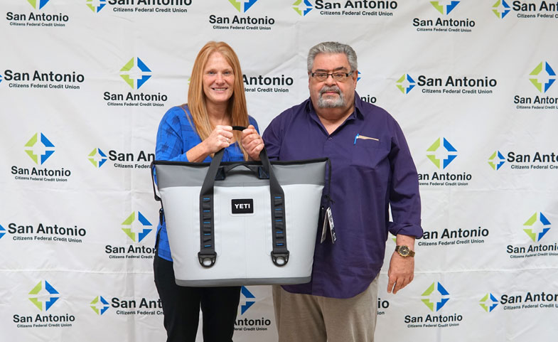 Picture of Carrie Carlberg, VP & San Antonio Area Manager presenting Bruce Santos with his prize of a Yeti Cooler. Congrats to Bruce on winning our 2019 eStatement Contest!