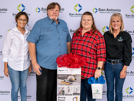 Picture of two SACFCU employees giving a prize of a Dyson Vacuum to the winner of our Bill Pay contest.