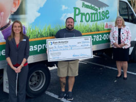 Image of two SACFCU Employees presenting a big check to a Thomas Promise Foundation Employee