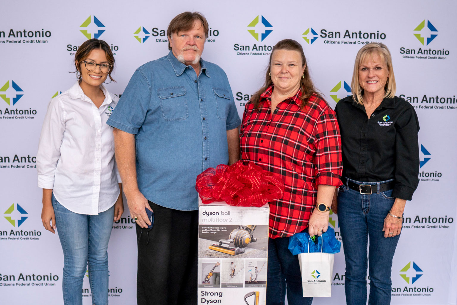 Two SACFCU employees giving a prize of a Dyson Vacuum to the winner of our Bill Pay contest.