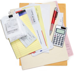 A pile of bills and receipts being calcualted over a few folders on a white background