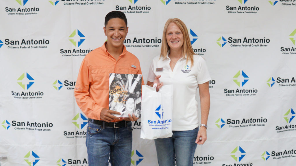 Picture of an SACFCU employee giving a prize to our Claim Your Youth Photo Contest Winner.