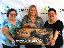 SACFCU's Debit Card Contest Winner holding Swagtron Smart Board