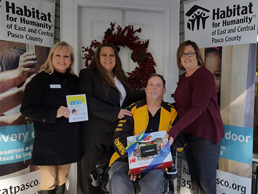 Image of SACFCU employees delivering a housewarming gift at the Habitat For Humanity Home Deciation in Dade City, FL.