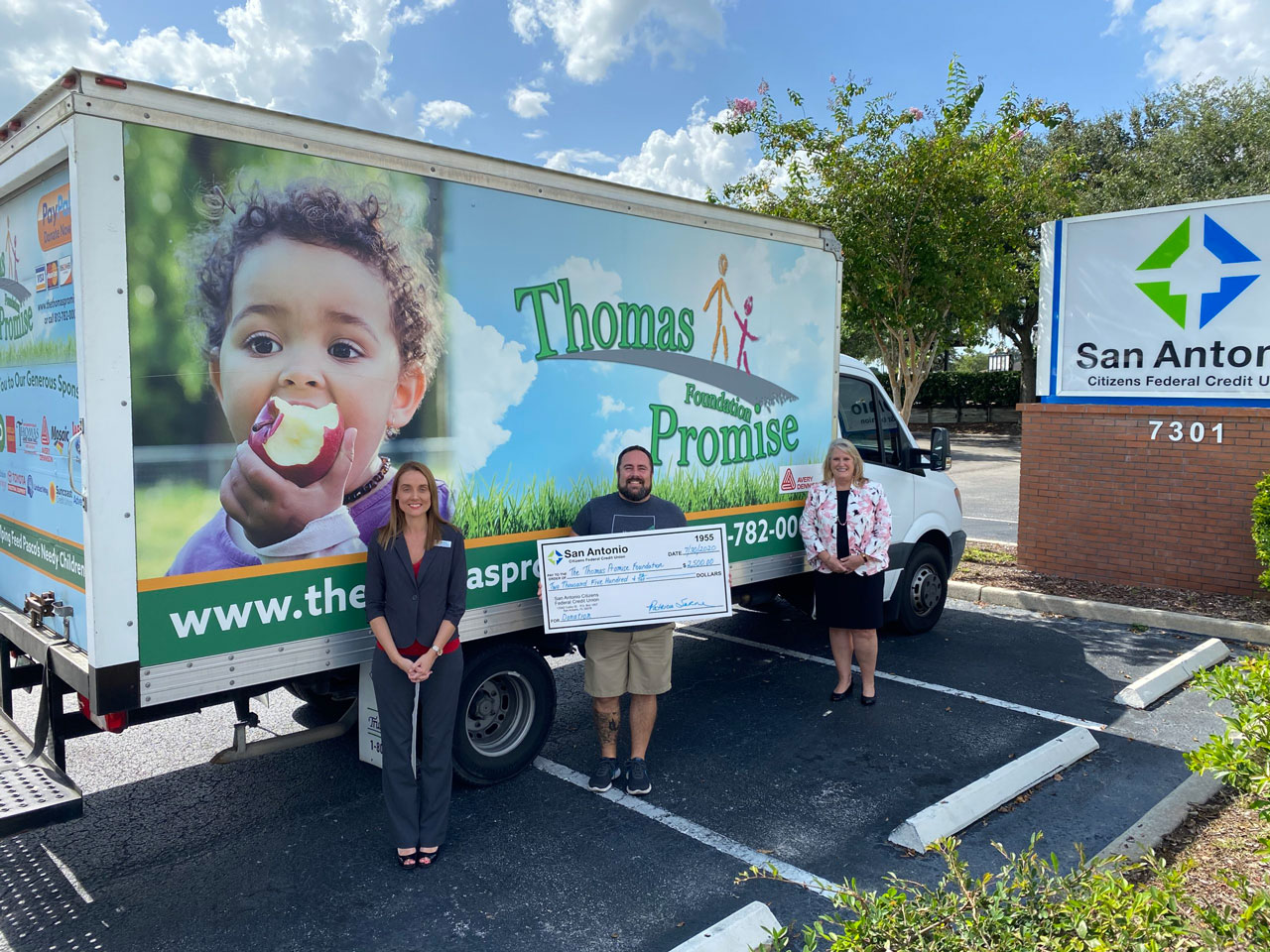 Two SACFCU Employees presenting a big check to a Thomas Promise Foundation Employee