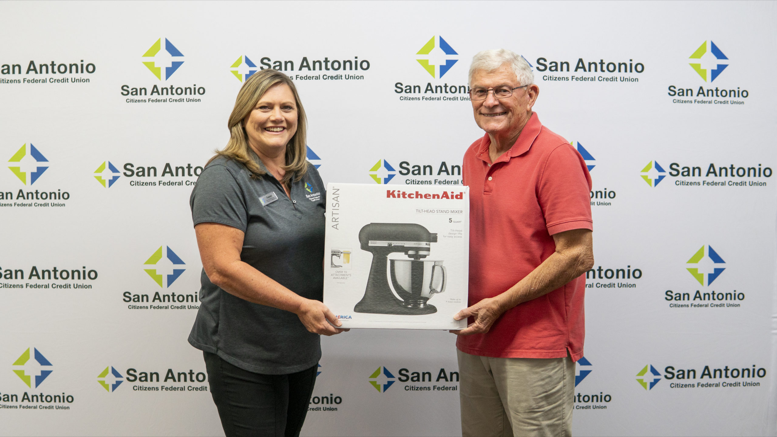 Picture of the Dade City Branch Manager along with the winner of SACFCU's Mobile Banking Contest.  Both of them are holding up the price of a Kitchenaid Stand Mixer