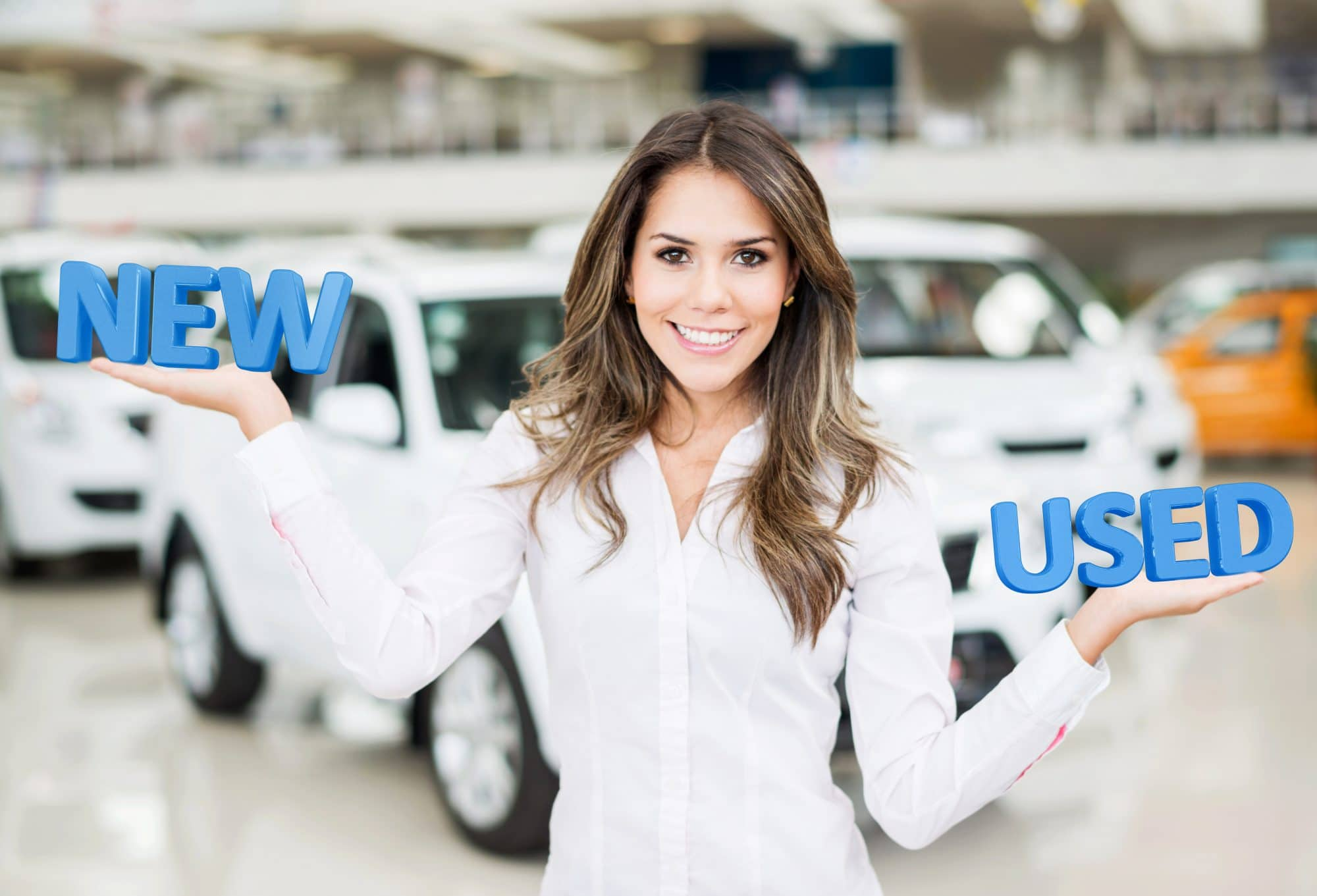 Image of woman in front of cars weighing the world new in one hand against used in the other