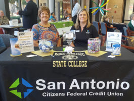 Employees manning our table at the student resource fair